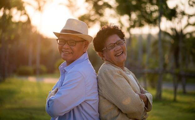 Ein glückliches älteres paar, das im garten lächelt und lacht, glückliche ehe