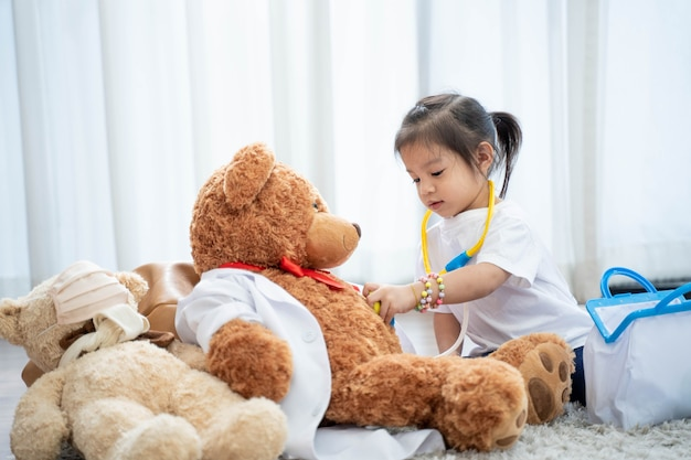 Ein glückliches asiatisches mädchen, das arzt oder krankenschwester spielt und ein stethoskop zum spielzeug hört.