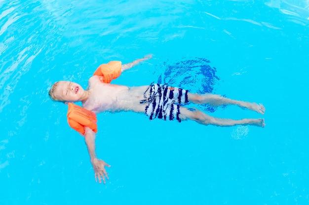 Ein glückliches baby liegt auf dem wasser oder lernt in armbinden in einem blauen wasserbecken schwimmen, das konzept der sommerferien und schulferien