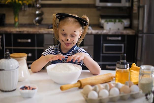 Ein glückliches baby mit einem kätzchenkostüm bereitet kekse für eine halloween- oder geburtstagsfeier vor