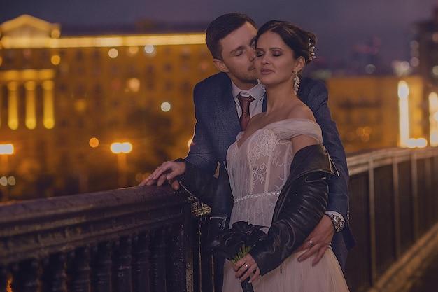 Ein glückliches brautpaar, das in der nachtstadt spaziert. stilvolle braut und bräutigam. hochzeitskonzept