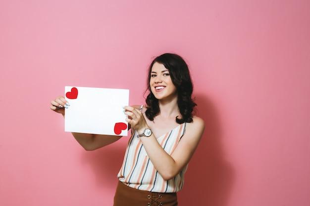 Ein glückliches brunettemädchen, das einen weißen freien raum mit einem herzen auf einer rosa wand hält