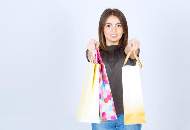 Ein glückliches frauenmodell, das viele einkaufstaschen auf weißem hintergrund hält.