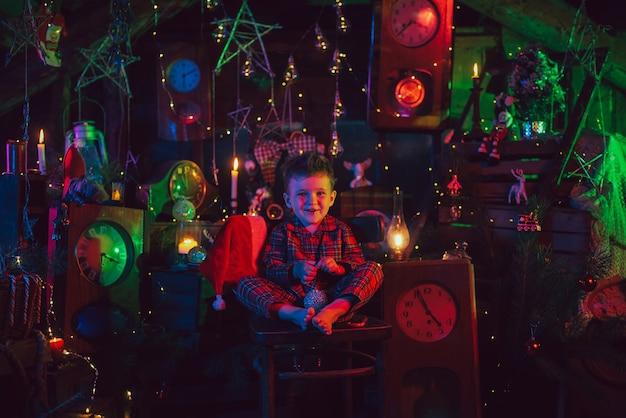 Ein glückliches junge-kind ist in der neujahrsdekoration. ein kind im weihnachtspyjama.