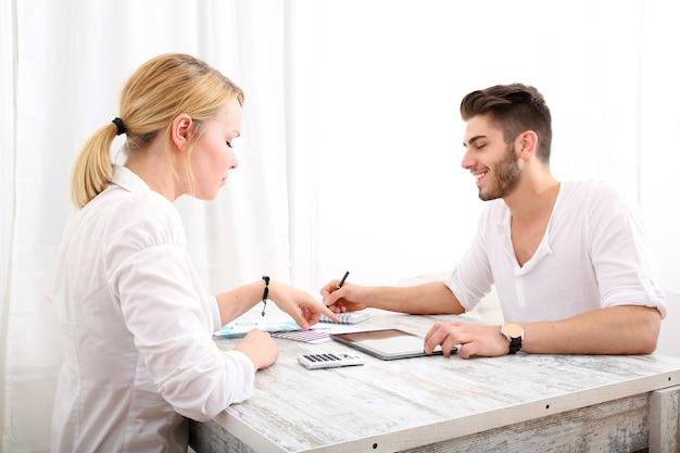 Ein glückliches junges paar, das ihre finanzielle situation zu hause organisiert.