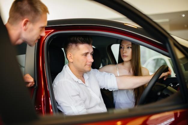 Ein glückliches junges paar wählt und kauft ein neues auto in einem autohaus. kauf eines neuen autos.