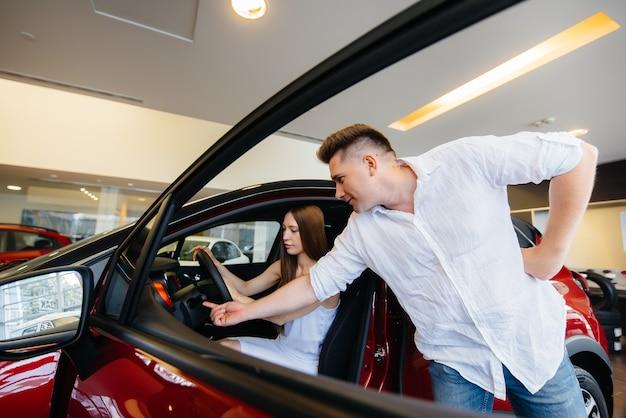 Ein glückliches junges paar wählt und kauft ein neues auto in einem autohaus. kauf eines neuen autos. Premium Fotos