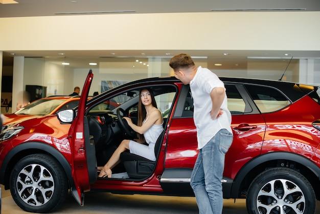 Ein glückliches junges paar wählt und kauft ein neues auto in einem autohaus