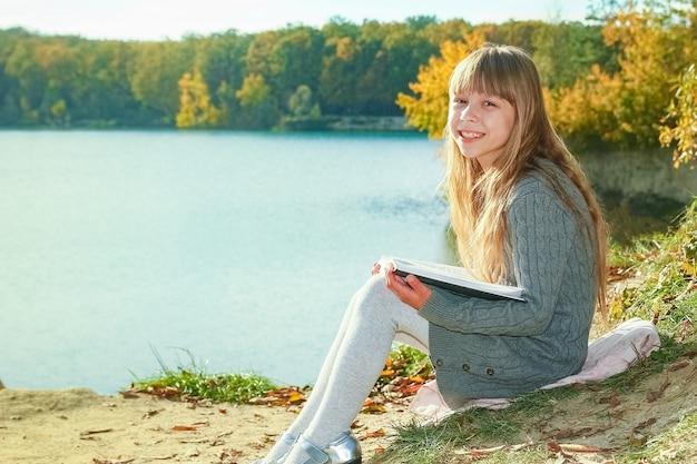 Ein glückliches kind, das buch über naturerziehung in parkreisen liest