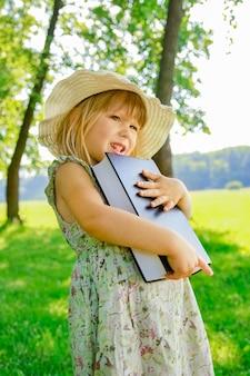 Ein glückliches kind mit einem buch über die natur der bibel im park