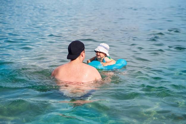 Ein glückliches kind mit seinem vater schwimmt in einem schwimmring im meer