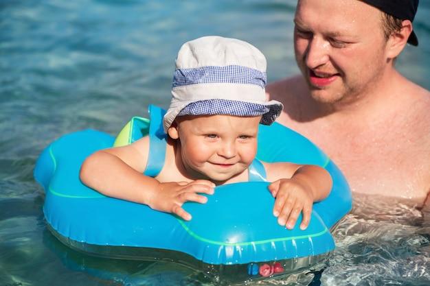 Ein glückliches kind mit seinem vater schwimmt in einem schwimmring in der adria