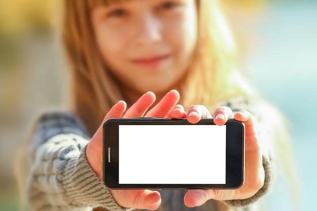 Ein glückliches kind mit telefon, das selfie in der natur in der parkreise nimmt