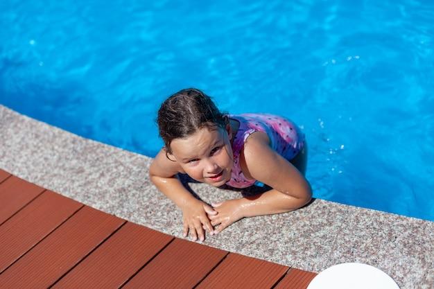 Ein glückliches kind springt auf den beckenrand und genießt einen heißen sonnigen tag