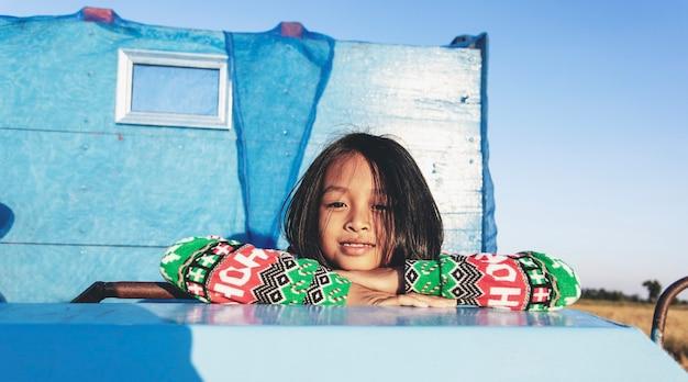 Ein glückliches kleines asiatisches mädchen auf einem blauen alten auto auf dem feld am abend