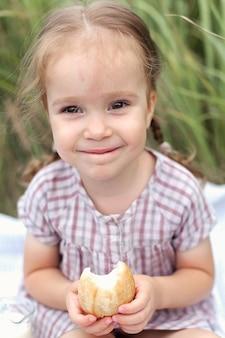 Ein glückliches kleines mädchen auf einem weizenfeld mit brot, lächelnd und in die kamera schaut. sommerwanderungen.