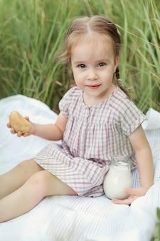 Ein glückliches kleines mädchen auf einem weizenfeld mit brot und einem krug frischer milch. sommerwanderungen im dorf. glückliche kindheit.