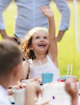Ein glückliches kleines mädchen, das im sommer im garten geburtstag feiert, partykonzept.