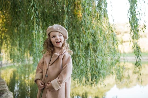 Ein glückliches kleines mädchen in einem beigen mantel und einer baskenmütze steht in der nähe eines weidenbaums