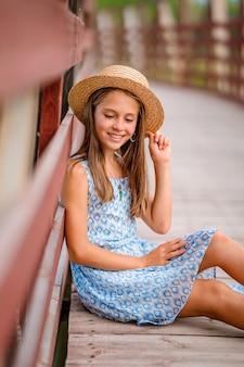 Ein glückliches kleines mädchen in einem blauen kleid in einem sommergarten mit einer holzbrücke