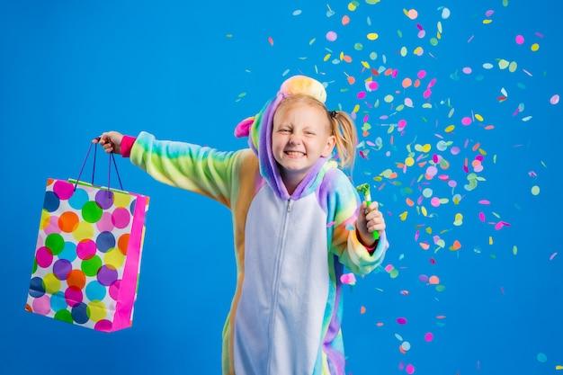 Ein glückliches kleines mädchen in einem einhorn-kigurumi hält eine geschenktüte