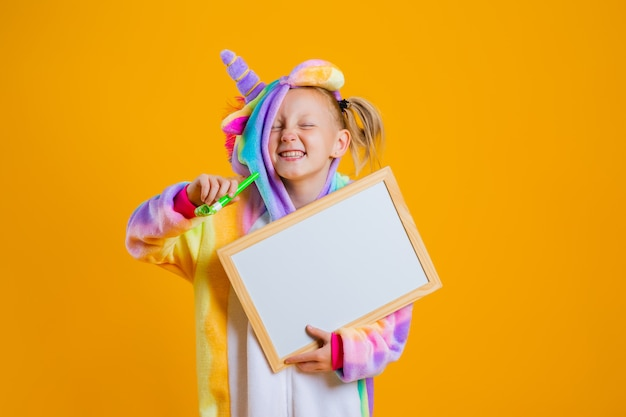 Ein glückliches kleines mädchen in einem einhorn-kigurumi hält eine leere tafel für text an einer gelben wand