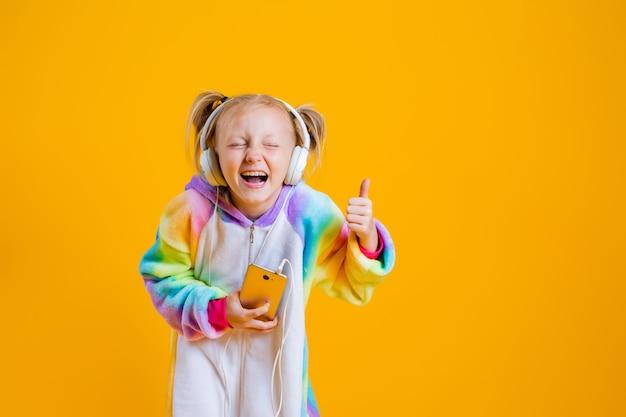 Ein glückliches kleines mädchen in einem kigurumi-einhorn hört musik in kopfhörern, die ein smartphone halten