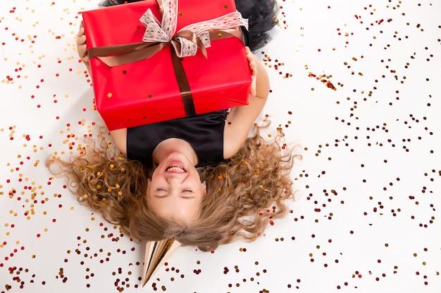 Ein glückliches kleines mädchen liegt auf einem weißen hintergrund mit einer geschenkbox und einer kappe für ihren geburtstag.