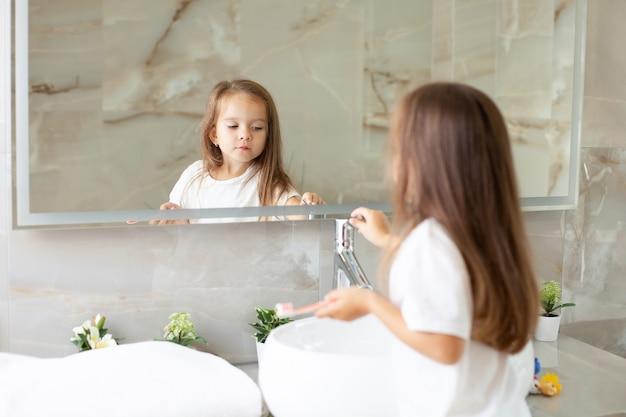 Ein glückliches kleines mädchen putzt sich vor einem spiegel im badezimmer die zähne. morgenroutine. hygiene. foto in hoher qualität