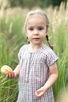 Ein glückliches kleines mädchen von 2-3 jahren in einem kleid und mit zöpfen auf einem weizenfeld mit brot an einem sommertag steht und schaut in die kamera. ernte.