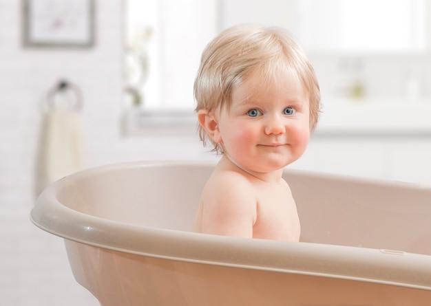 Ein glückliches kleinkind, das in der badewanne badet.