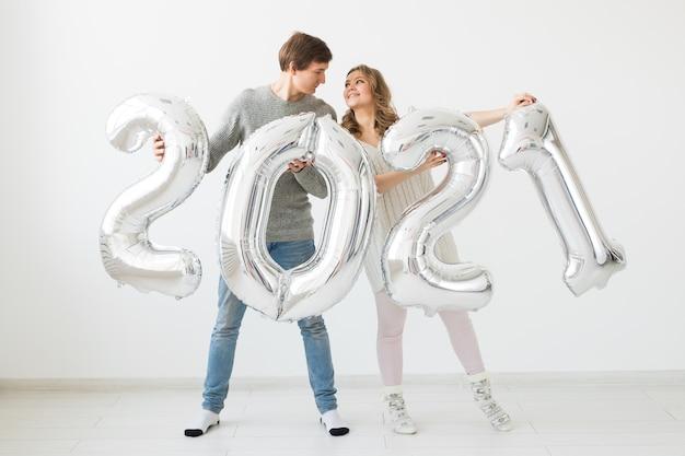 Ein glückliches liebespaar hält silberne 2021 luftballons