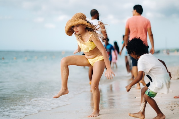 Ein glückliches mädchen in einem gelben badeanzug und einem strohhut spielt mit einem schwarzen jungen an einem strand von mauritius.