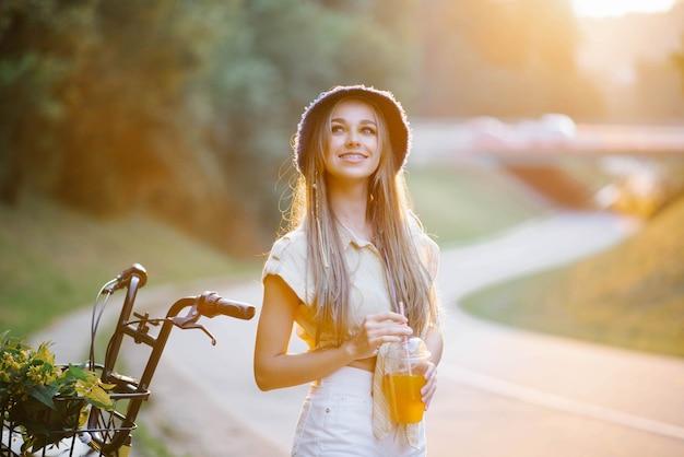Ein glückliches mädchen in weißen shorts und einer gelben bluse hält ein glas saft mit einem strohhalm auf dem hintergrund der straße in der nähe des waldes