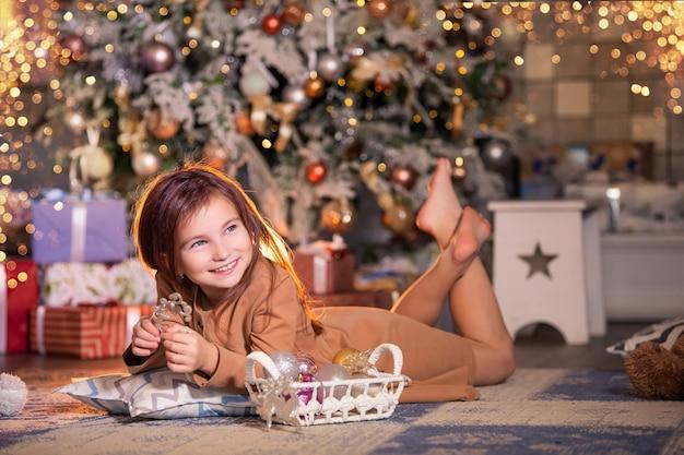Ein glückliches mädchen liegt vor dem hintergrund eines weihnachtsbaumes auf dem boden und hält eine weihnachtsdekoration in form eines hirsches in den händen.