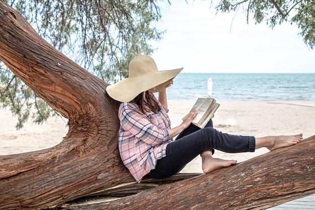 Ein glückliches mädchen liest ein buch auf einem baum. die person, die von allem abstrahiert ist. das konzept der entspannung und ruhe.