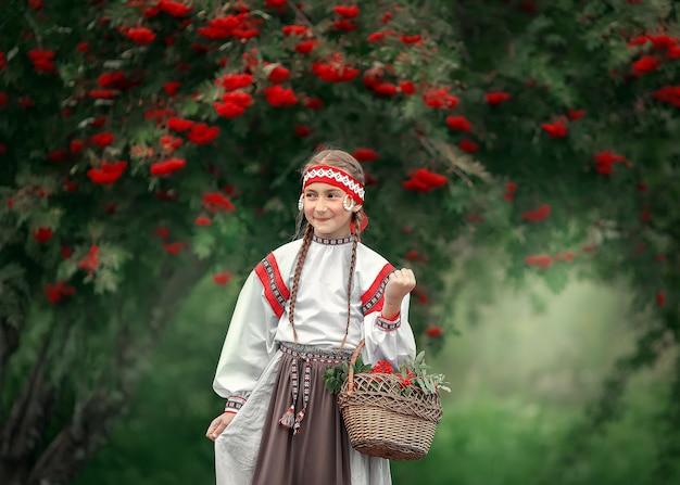 Ein glückliches mädchen mit einem korb voller ebereschenbäume in ihren händen