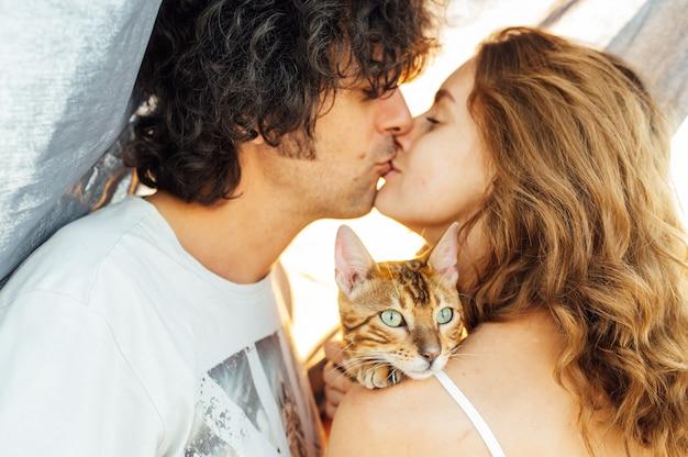 Ein glückliches mädchen mit einer katze im arm küsst sanft ihren freund.