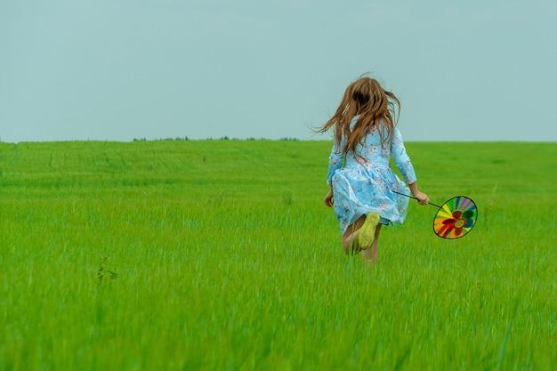 Ein glückliches mädchen mit langen haaren läuft über eine grüne wiese mit einer windmühle in den händen. konzept des sommers und der glücklichen kindheit.
