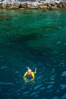 Ein glückliches mädchen schwimmt mit hilfe einer gelben nudel auf dem mittelmeer. marmaris, türkei,