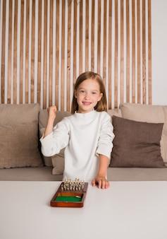 Ein glückliches mädchen sitzt hinter dem sofa und hat eine schachpartie gewonnen