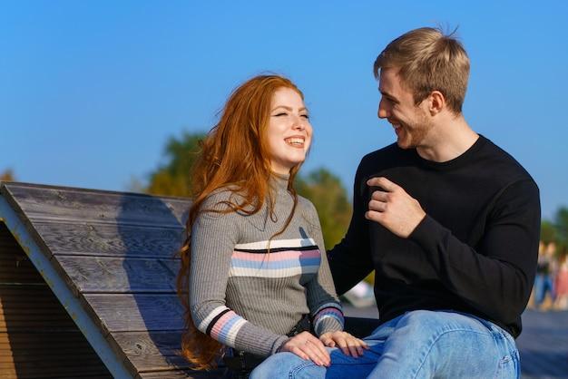 Ein glückliches paar, ein mann und ein mädchen mit langen roten haaren, sitzen auf einem holzdeck in einer umarmung junger mann und frau kaukasischer abstammung in freizeitkleidung an einem warmen sonnigen tag umarmen