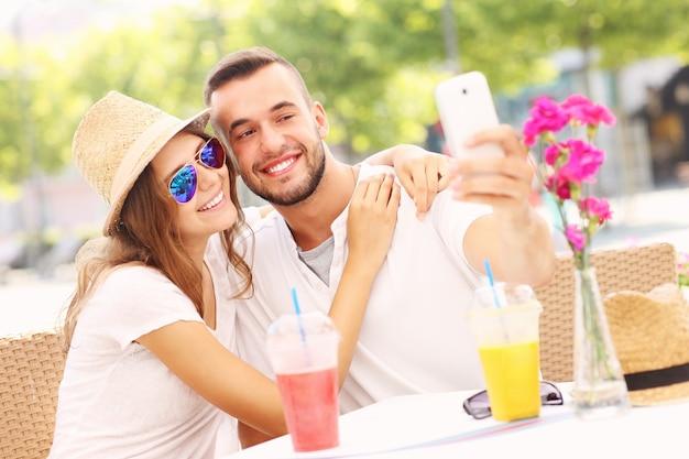 Ein glückliches paar macht selfie in einem café self