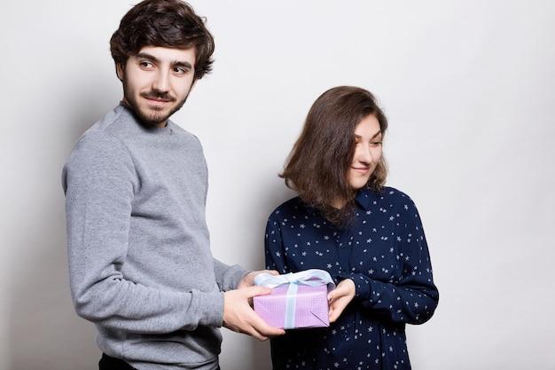 Ein glückliches paar mit geschenk. ein hipster-typ, der seiner freundin ein geschenk überreicht und beiseite schaut. junger mann und frau