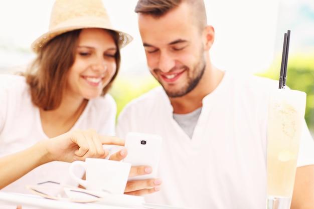 Ein glückliches paar mit ihren smartphones in einem café
