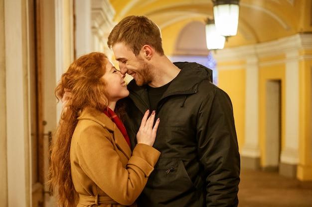 Ein glückliches paar steht abends in den festlichen lichtern in einer umarmung auf der straße