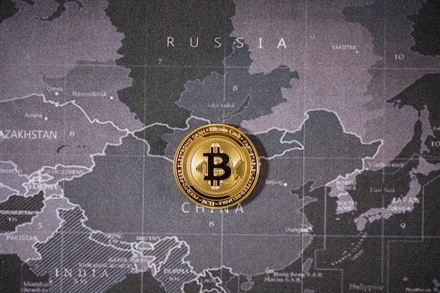 Ein gold-bitcoin wird auf der weltkarte über dem namen des landes gelegt. kryptowährung bitcoin, die zukünftige münze, ist die wichtige währung, um alles in der globalen weltzukunft zu bezahlen.