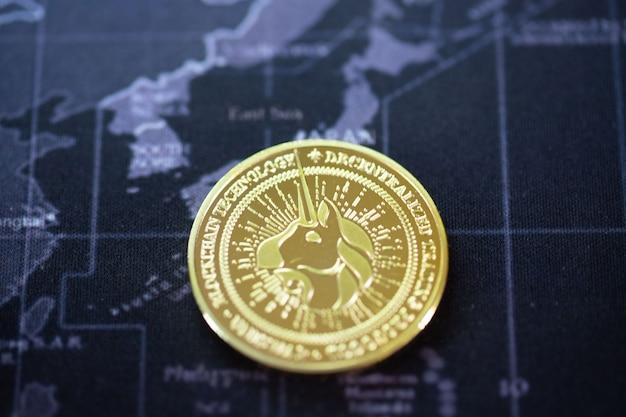 Ein gold-bitcoin wird auf der weltkarte über dem namen des landes gelegt. kryptowährung bitcoin die zukünftige münze, neues virtuelles geld, um alles in der globalen weltzukunft zu bezahlen.