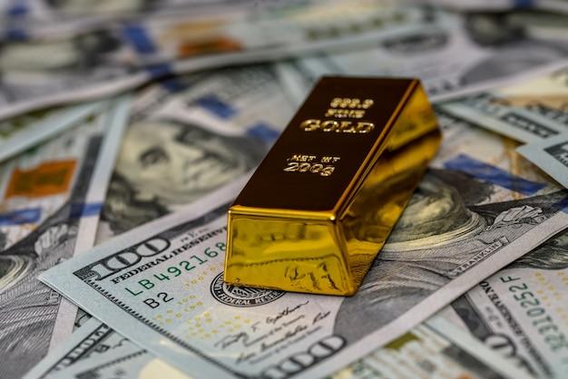 Ein goldbarren mit dollar-banknoten-nahaufnahme