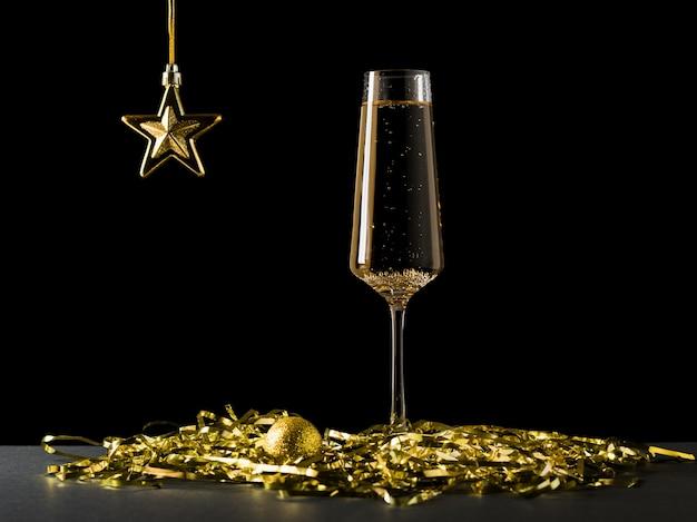 Ein goldener stern und ein glas wein mit ein paar luftschlangen auf schwarz.